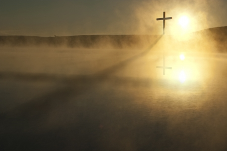 This Sunrise Cross on a misty lake casts a lengthy shadow and reflection on this calm Easter Morning Illustration