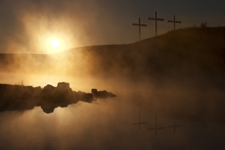 Dramatic religious photo illustration of Easter Sunday Morning reflecting a prayerful moment as a warm sun rises over a foggy lake, and three crosses on a hill reflect in the water below