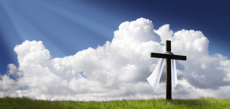 This dramatic Easter Morning Sunrise panorama with blue sky, sunbeams, and large cross on a grass covered hill makes a great banner cover for print or web