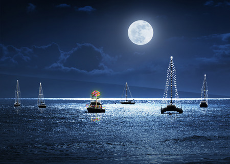 This photo illustration depicts a warm tropical Christmas Holiday scene with full moon boats decorated with lights and a Palm Tree as a Christmas Tree.