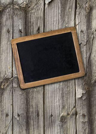 Front view, upright format, of a blank blackboard over a weathered wooden surface