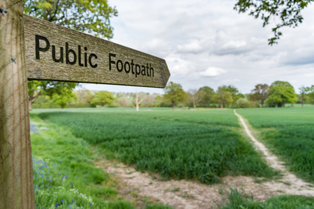 Photo for Close up view of a public footpath sign in Surrey, UK. The fingerpost points to a muddy path crossing a field to trees in the distance under a cloudy sky, taken with a shallow depth of field. - Royalty Free Image