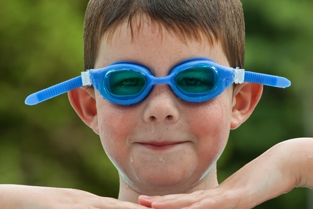 Boy in blue swim goggles having a fun time at the pool