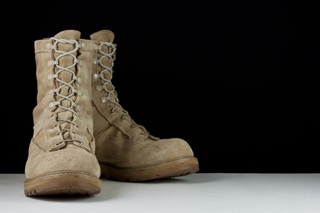 Pair of tan leather Army combat boots placed in angled position on black background.