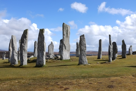 Standing stone circle on green grass with a blue cloudy sky at Callanish, Isle of Lewis, Scotland, UK.
