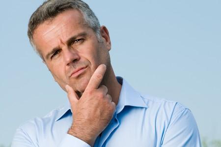 Perplexed mature man looking at camera outdoor