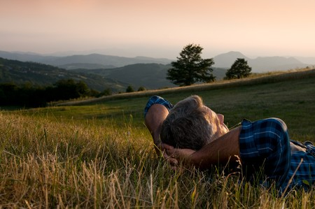 Closeup view of mature man taking a break and relax in a meadow in the wonderful warm light of the sunset