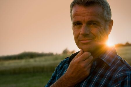 Photo pour Mature man taking a break and relax in a meadow in the wonderful warm light of the sunset - image libre de droit