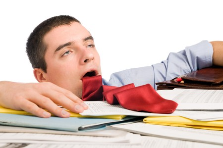 Young exhausted businessman with his necktie like a sticked out tongue lying down heap of documents.