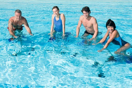 Happy smiling fitness people exercising with acqua bike in a swimming pool