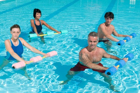 Happy active fitness people doing exercise with aqua dumbbell in a swimming pool