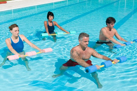 Group of healthy people doing aqua gym exercise with water dumbbell in a swimming pool