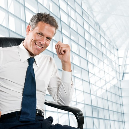Photo pour Smiling satisfied businessman looking at camera sit in his chair at office - image libre de droit