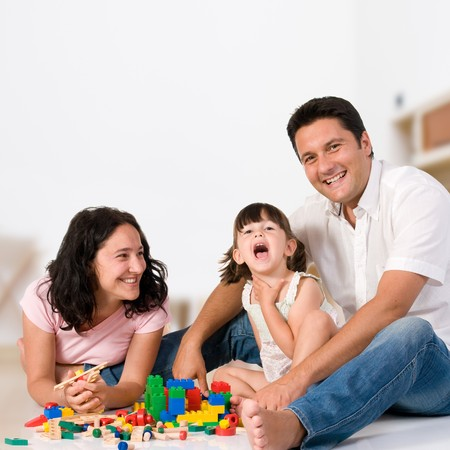 Photo pour Happy family with parents and daughter playing with colorful blocks inside at home - image libre de droit