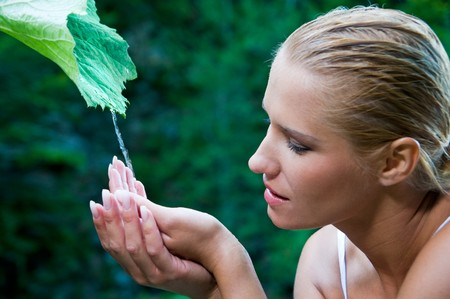 Beatiful young woman with open hands take fresh flowing water from a green leaf in the nature. Symbol of harmony and body care