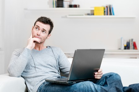 Doubtful young man looking up while working on laptop at home