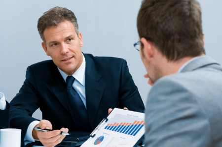 Mature businessman showing growing chart in a meeting discussion at office