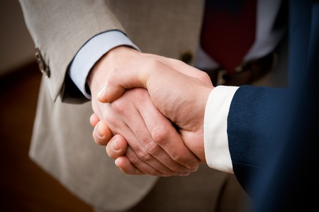 Two professional businessman giving handshake in the office, closeup selective focusの写真素材