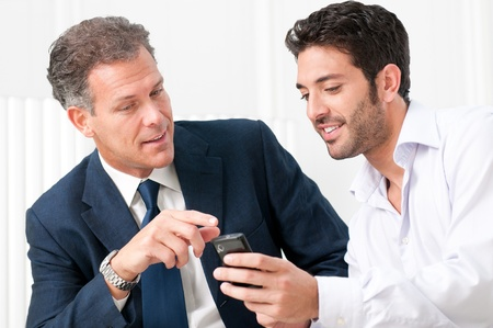 Two businessmen discussing together on a news on a smart phone