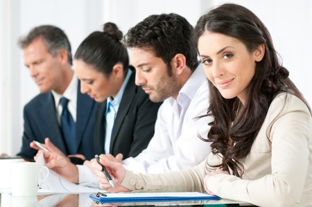 Satisfied smiling business woman looking at camera with working colleagues in office