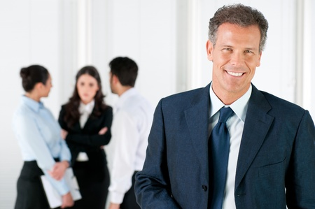 Photo pour Modern mature businessman smiling and looking at camera with his colleagues in the background at office - image libre de droit