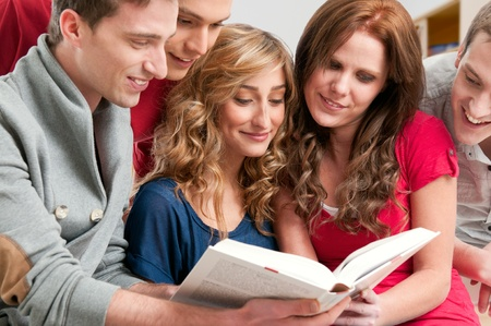 Happy young college students studying together on a textbook in a library