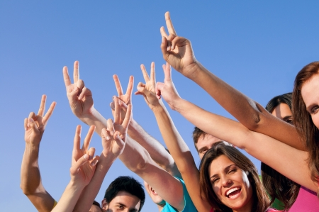 Happy group of young friends showing victory hand sign over blue sky