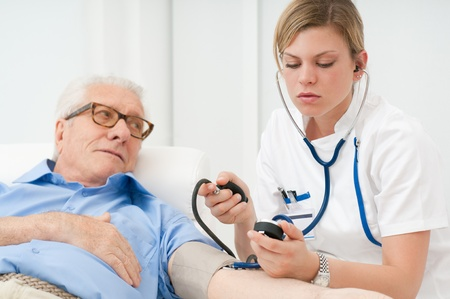 Photo pour Young nurse checking the blood pressure of her old senior patient at hospital - image libre de droit