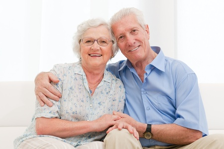 Happy smiling senior couple embracing together at homeの写真素材