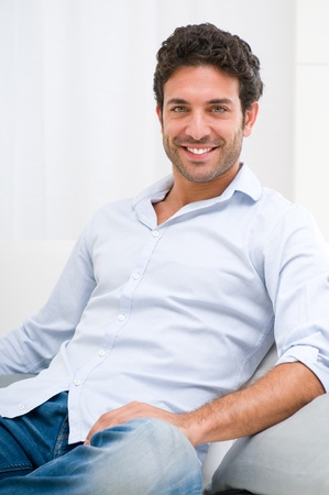 Foto de Happy smiling young man relaxing on sofa at home - Imagen libre de derechos