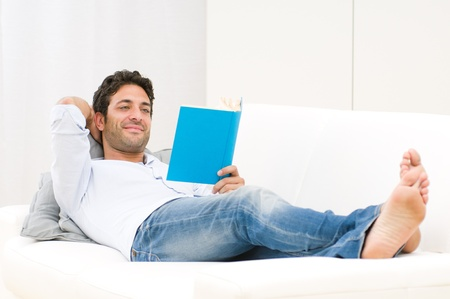 Smiling relaxed man reading a book lying on sofa