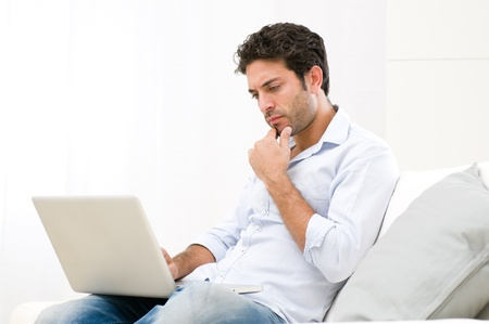 Worried young man looking at his laptop computer with pensive expression