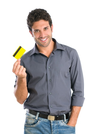 Happy smiling young man holding a credit card isolated on white background
