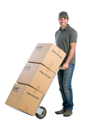 Photo pour Smiling young delivery man moving boxes with dolly, isolated on white background - image libre de droit