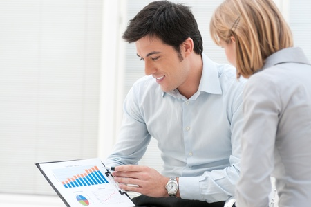 Satisfied business man showing and pointing at growing chart with his colleague at office