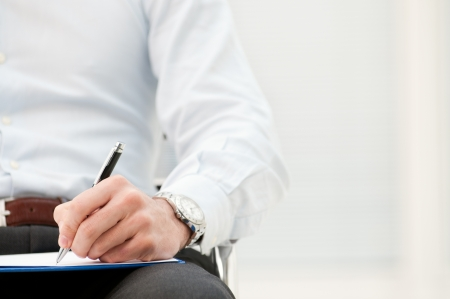 Photo pour Closeup of business man writing form on clipboard at office - image libre de droit