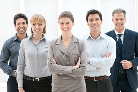 Happy smiling group of business people standing together at office