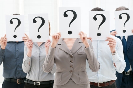 Business team hiding their faces behind question mark signs at office