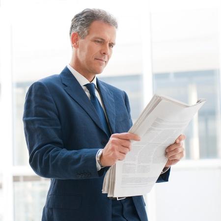 Photo pour Mature business man reading news in the office - image libre de droit