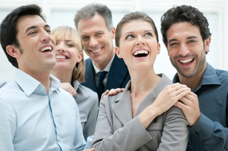 Foto de Happy business team smiling and laughing together at office to celebrate a success - Imagen libre de derechos