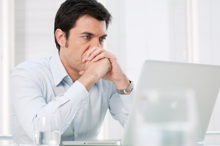 Pensive absorbed business man watching at computer laptop with worried expression
