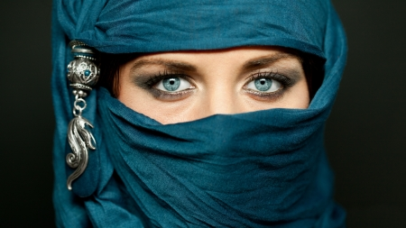 Portrait of an arabic young woman with her beautiful blue eyes in traditional islamic cloth niqab