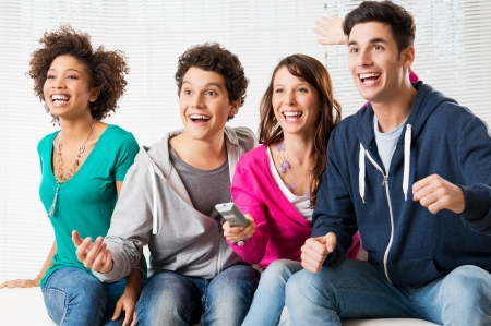 Happy Group Of Young Friends Watching Television And Supporting Their Team