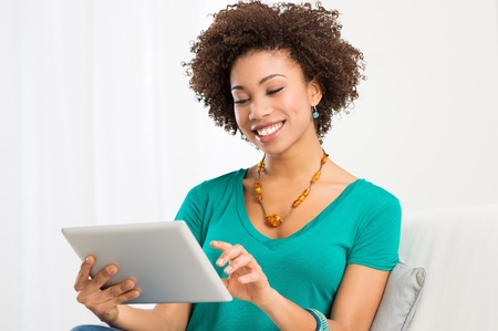 Portrait Of Young Happy African Woman Looking At Digital Tablet