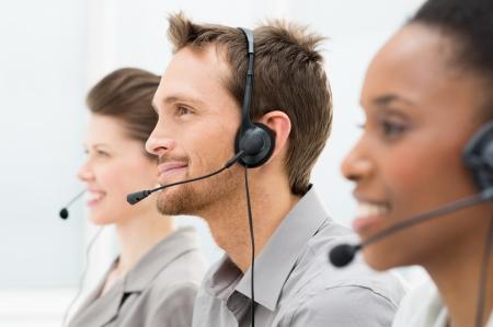 Photo pour Closeup Of Happy Telephone Operators In A Row - image libre de droit