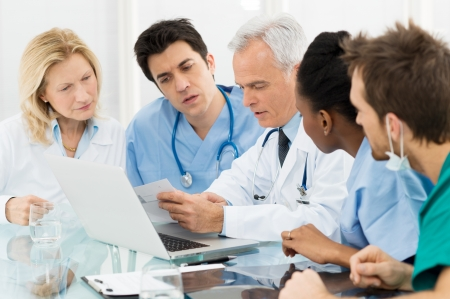 Team Of Expert Doctors Examining Medical Reports at Hospital