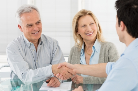 Senior Happy Couple Shaking Hand With Financial Advisor