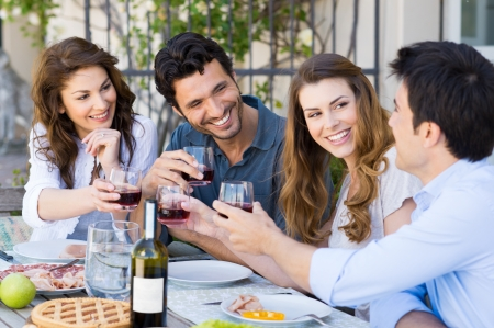 Photo pour Group Of Happy Young Friends Toasting Wine Glass Outdoor While Having Lunch - image libre de droit