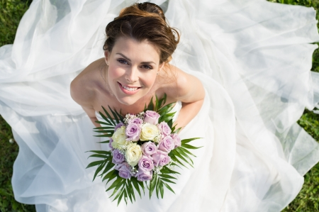 Foto de High View Portrait Of Beautiful Happy Bride Sitting On The Grass - Imagen libre de derechos