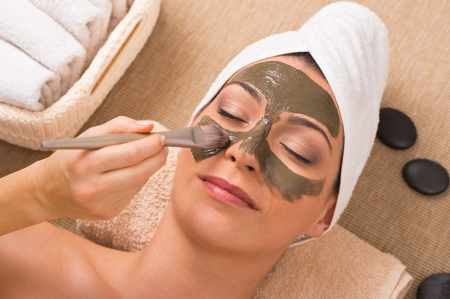 Close Up Of A Beautician Who Apllies The Facial Treatment To a Beautiful Woman In Day Spa